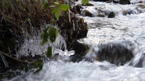 Blured then focused icicles over mountain stream Footage