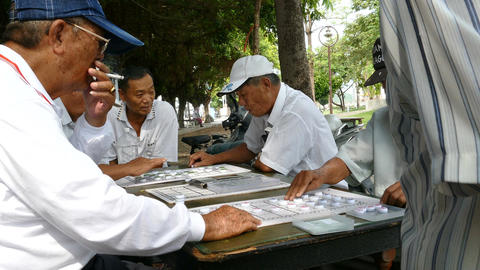 Men playing a board game in the street Footage
