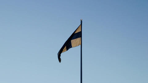 Finnish national flag against a blue sky with warm sunlight from the back Footage