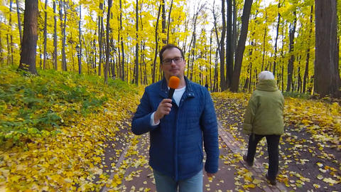 Adult journalist with microphone working in autumn park Live Action