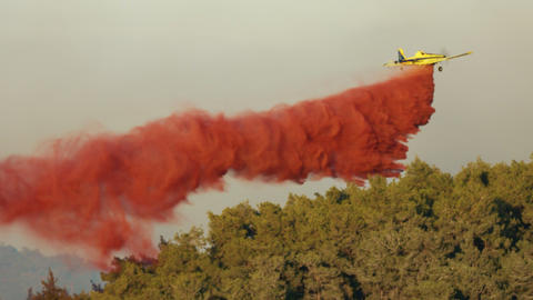 Fire fighter plane drops fire retardant on a forest fire 5 Live Action