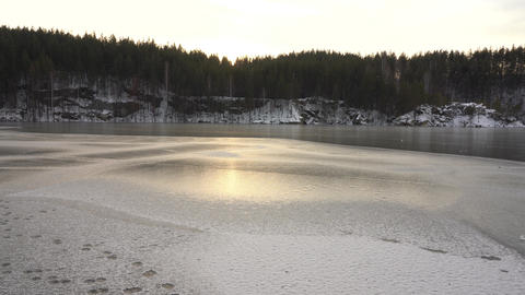 The traveler looks at a frozen mountain lake. EXTREME OF TRAVELING IN THE WILD Live Action
