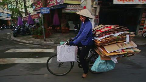 Closeup Rider on Bike Carries Cardboard Pile along City Street Footage