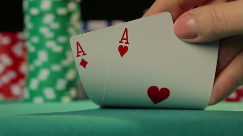 Closeup of poker player's hand checking cards, holding two aces, chance to win Live Action