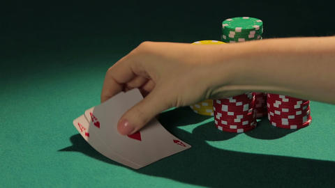 Professional poker player showing pair of aces to rival, casino chips on table Footage