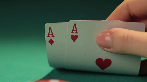 Poker player looking at pile of chips and pair of aces in hand, making decision Footage