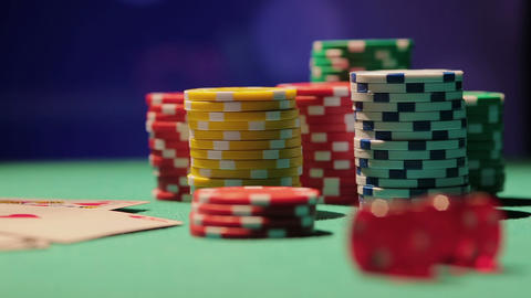 Rack focus shot of pile of poker chips and dice on table, casino background Footage