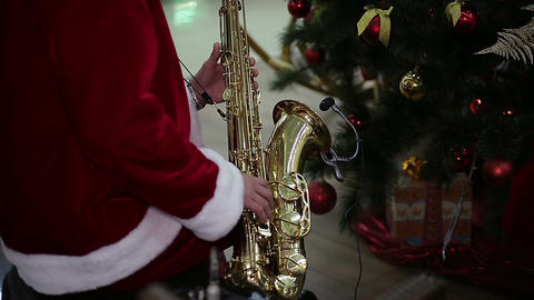 Saxophonist in Santa Claus suit playing merry Christmas carol near New Year tree Footage