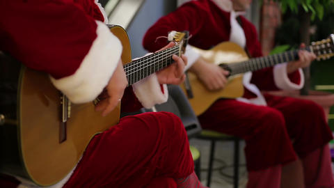 Guitar players performing merry songs for festive mood of shopping mall visitors Footage