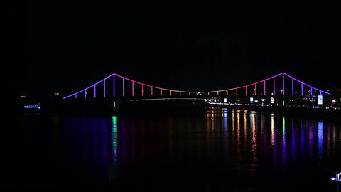 Beautiful night cityscape, illuminated bridge across river shining in darkness Footage
