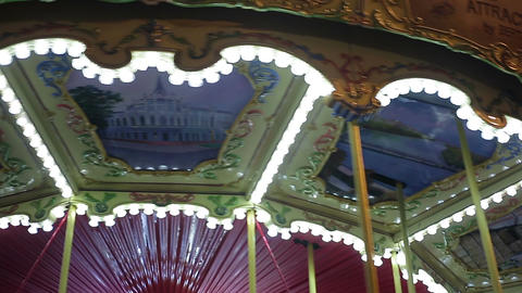 Illuminated merry-go-round rotating at amusement park, happy childhood memories Footage
