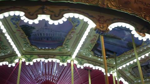 Illuminated merry-go-round rotating at amusement park, happy childhood memories Footage