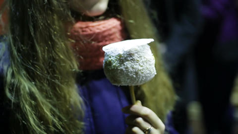 Romantic young woman eating sweet candy apple at date during outdoor festival Footage