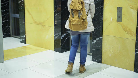Anxious woman waiting for elevator, pressing button nervously, late for meeting Footage