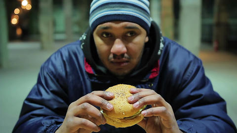 Thoughtful man is going to eat burger. Unhealthy meal. Health damage. Hunger Live Action