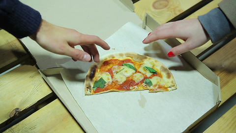 Man takes the last piece of pizza at lunch. Gender inequality. Disappointment Footage
