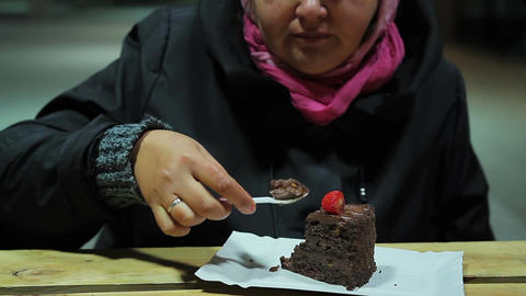 Unhealthy food. Dessert at dinner. Plump woman eating brownie with strawberries Footage