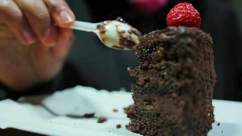 Desserts, sweets. Plump woman eating sugary brownie with strawberry. Diabetes Footage