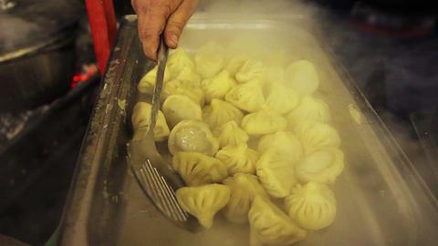 Oriental cuisine. Street food-fest. Seller taking tasty and appetizing khinkali Footage