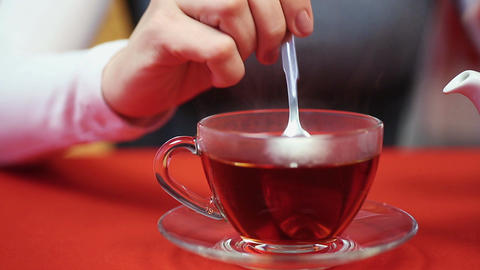 Relaxing evening at home. Woman pouring tea in a cup. Hot and tasty beverage Footage