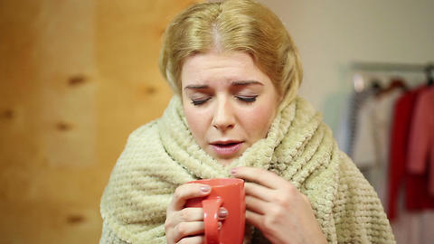 Diseased girl warming herself with hot tea, feeling sick. Healthcare, illness Footage