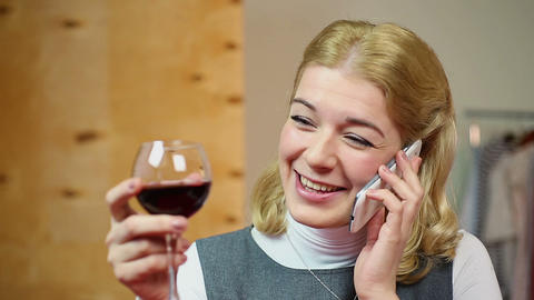 Laughing blond woman talking on mobile phone, drinking wine and smiling Footage