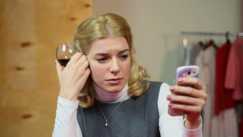 Sad melancholic woman drinking wine and sending a text message to her beloved Footage
