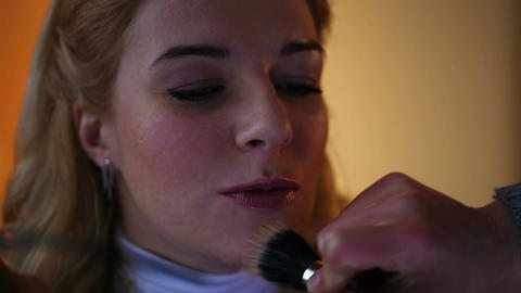 Happy client sitting in beauty salon. Skilled artist applying makeup on skin Footage