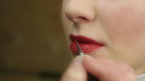 Process of applying red lipstick at makeup studio. Beautiful female lips closeup Footage
