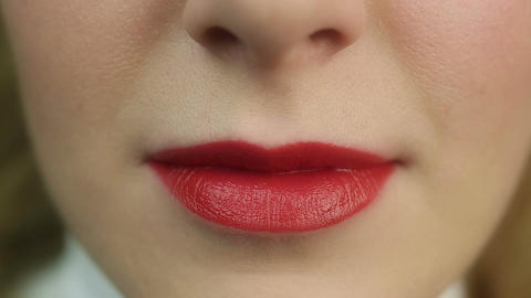 Seductive beautiful female flirting and biting lip. Perfect make-up. Red lips Live Action