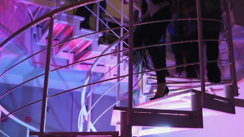 Many people climbing and going down the stairs in night club. Movement Footage