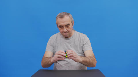 A Elderly man solving Rubik. Isolated on blue Live Action