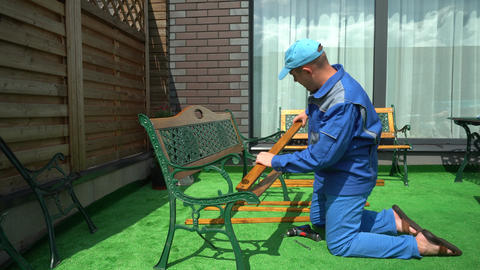 Man working assemble bench Wooden Planks. Worker in work wear on artificial lawn Live Action