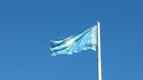 Flag of the Republic of Kazakhstan on the flagpole waving on background blue sky Footage