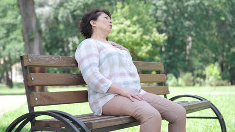 Ill Caucasian senior woman having heart attack sitting on bench in summer park Live Action