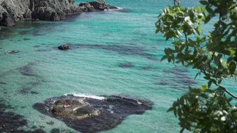 Beautiful seascape with a gentle blue and blue ocean with a rocky coast. Footage Live Action