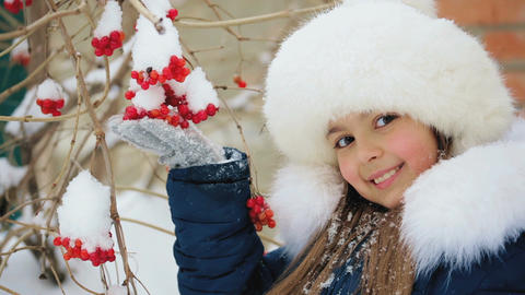 Girl Holds a Bunch of Viburnum Outdoors in Winter GIF