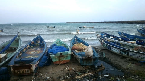 Beach of Indian ocean. Fishing boats waiting out at sea Footage