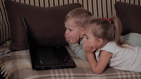 family, game, quarantine, childhood concepts - Two happy young children watching Live Action