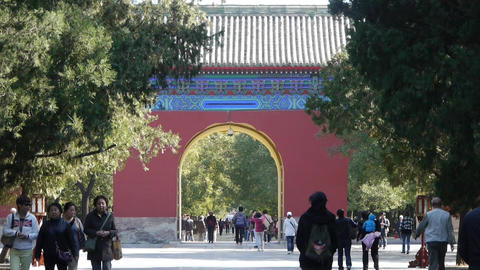 Asian People walk in cypress trees park,China Beijing red door ancient buildings Footage