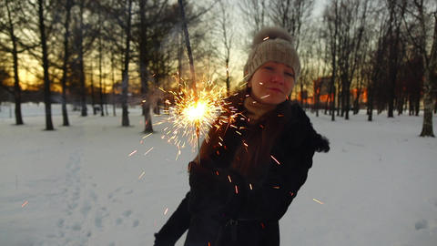 Girl look from behind burning sparkler, slow motion shot at winter park Footage