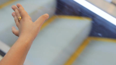 Closeup on little girl hand holding an escalator going down in shopping mall Footage