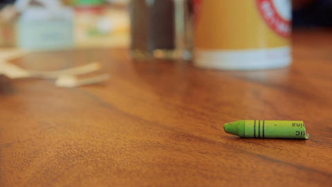 Green color pastel crayon rolls on brown wooden table Footage