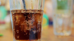 Glass with cola and ice on a table Footage