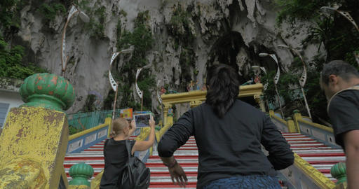 Young woman at Batu Caves, Malaysia climbs the stairs and takes pictures on tabl Footage