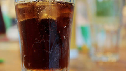 Pouring cola into a glass with ice on a table