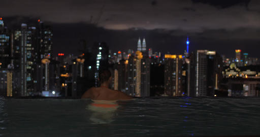 View of woman swimming in the pool on the skyscraper roof and then watching on n Footage