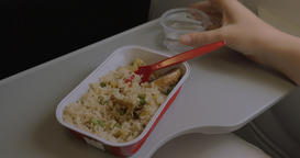 In plane on table is disposable tableware with a dish of rice and chicken and a  Footage