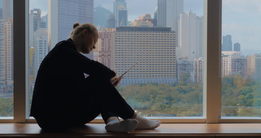 Young woman sitting on the windowsill, using tablet and looking the window. Hong Footage