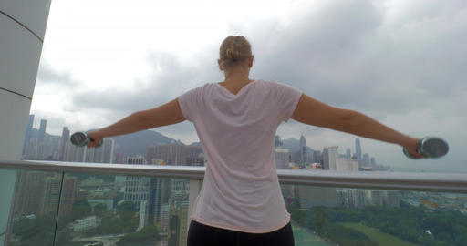 In Hong Kong, China on the terrace a young girl does exercises with dumbbells sp Footage